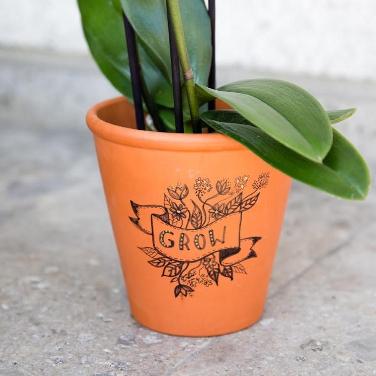 Handlettering auf einem Blumentopf: grow