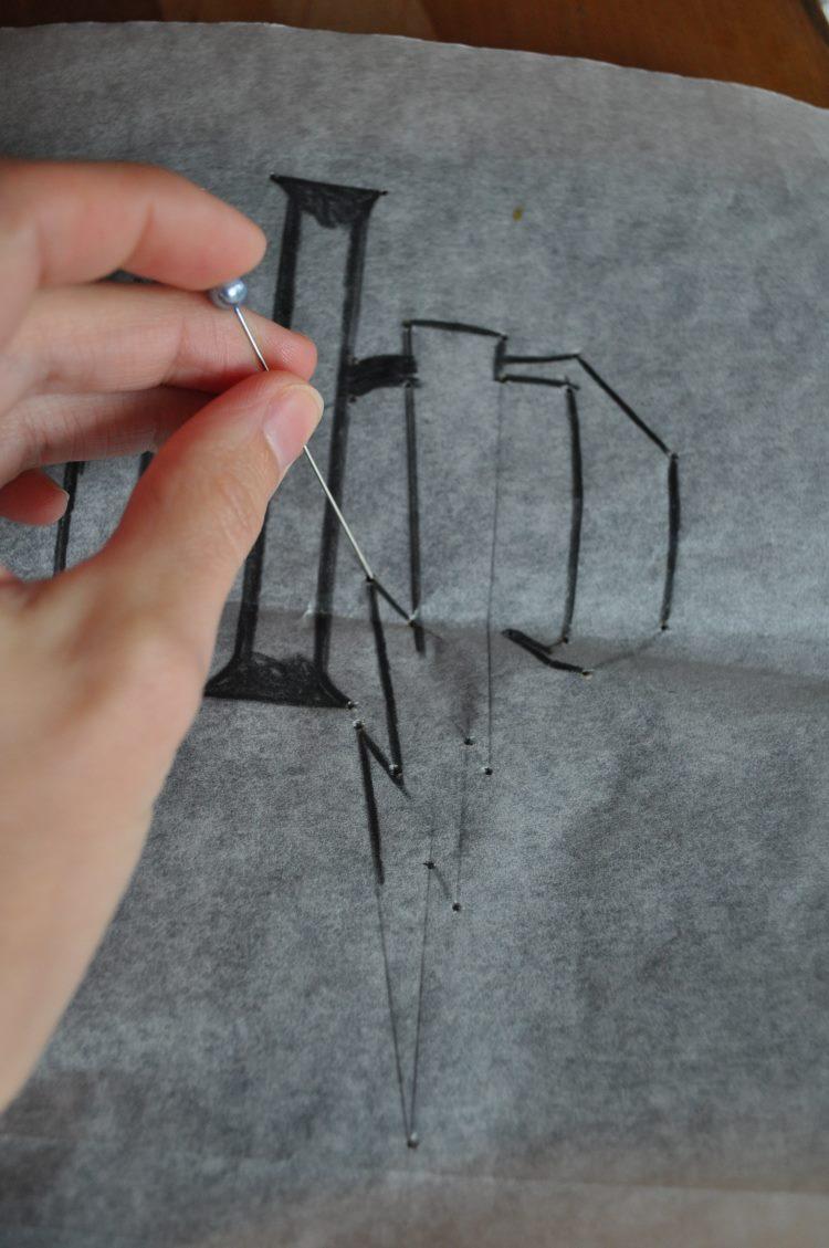 Vorzeichnen bzw. vorstechen mit einer Nadel für ein Lettering auf einem T-Shirt