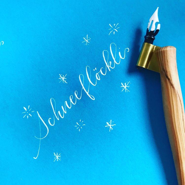Schneeflöckli - Kalligrafie in weiss auf blauem Papier