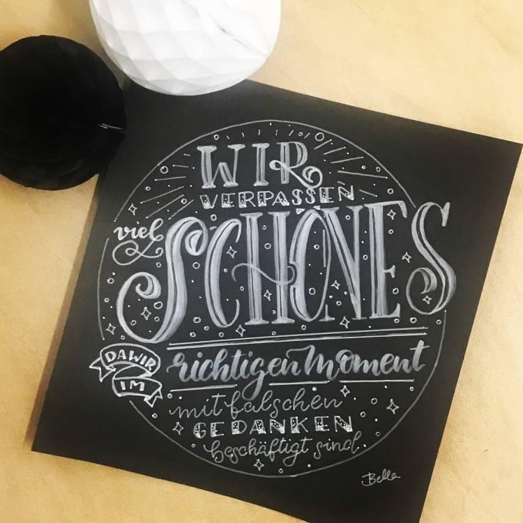 Handlettering in weiss auf schwarz: wir verpassen viel Schönes da wir im richtigen Moment mit falschen Gedanken beschäftigt sind