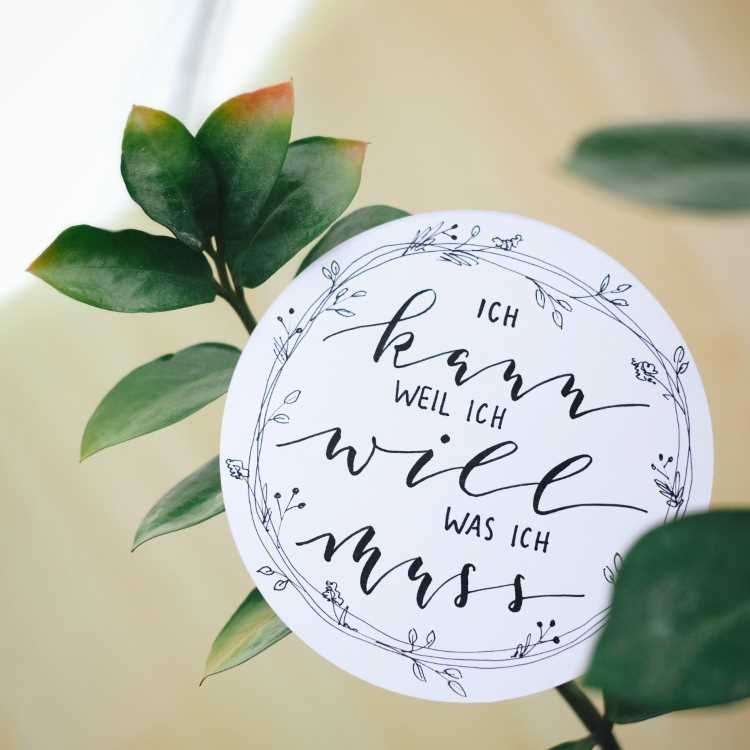 Handlettering in einem Kreis mit einem Blumenkranz - ich kann weil ich will was ich muss
