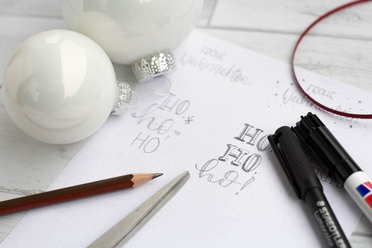 Skizzen für ein Lettering auf einer Weihnachtskugel