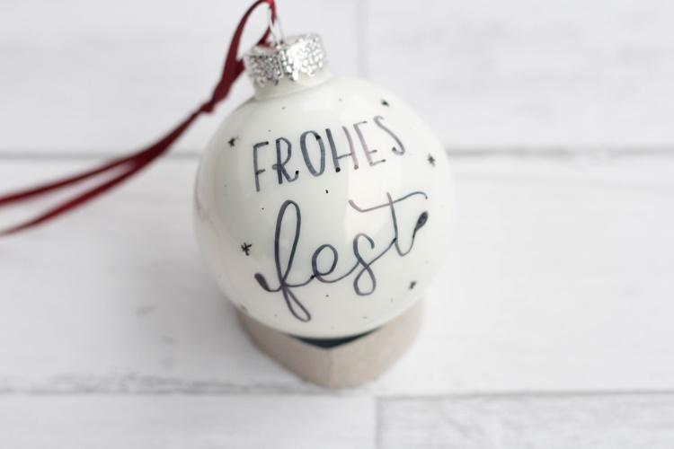 frohes fest - weisse Weihnachtskugel mit Handlettering drauf