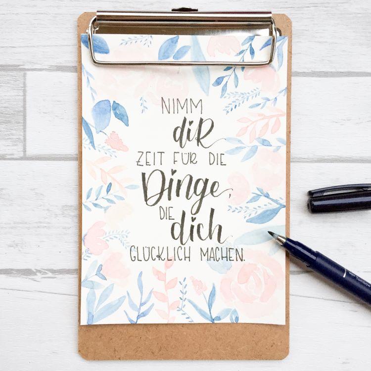 Handlettering Spruch mit Aquarell Blumen und Blättern im Hintergrund - NImm dir Zeit für die Dinge die dich glücklich machen