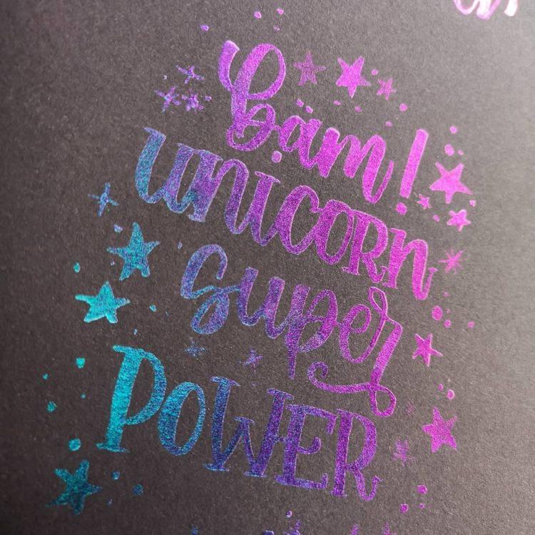 buntes Lettering mit Glitzer auf schwarzem Papier: bäm! Unicorn super Power