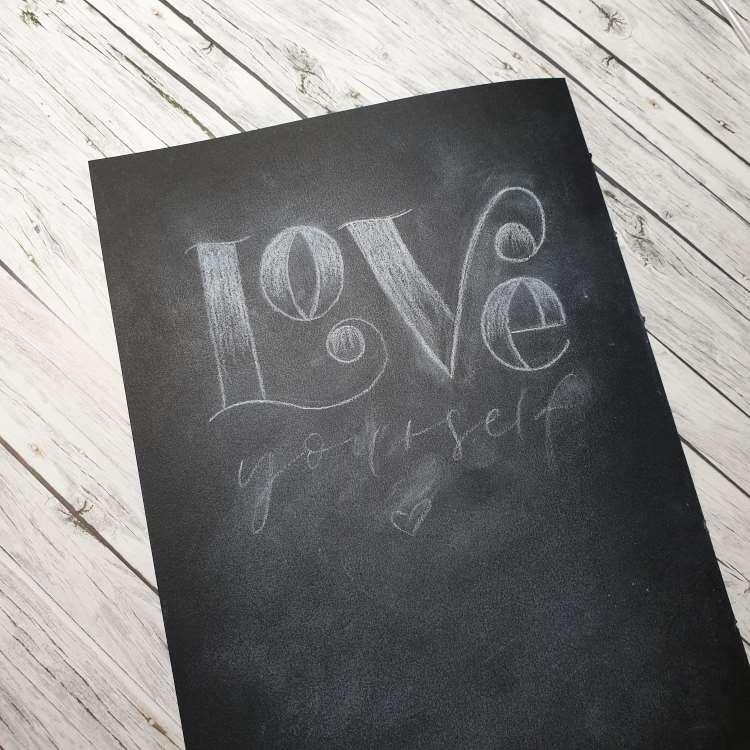 Love yourself - Skizze von einem Kreidelettering auf schwarzem Papier