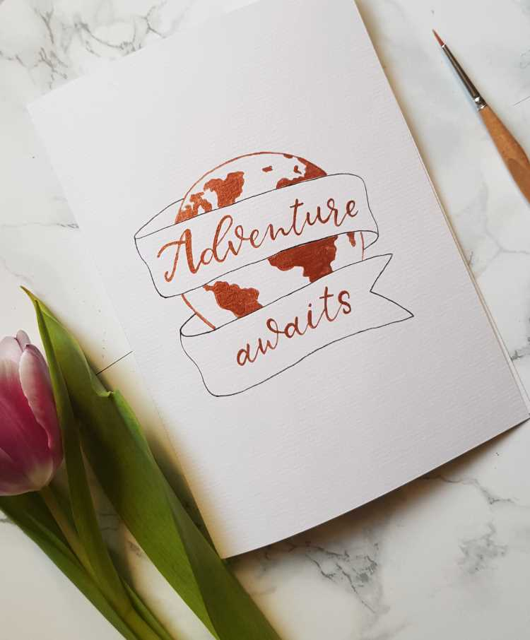 Brushlettering mit Erdkugel und Banner: adventure awaits