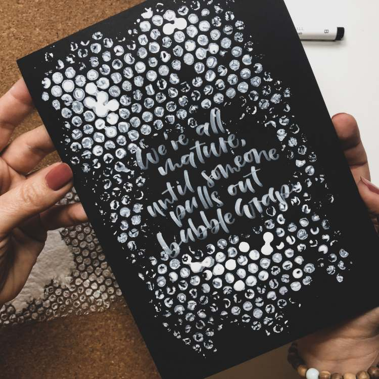 Handlettering in weiss mit einem Hintergrund aus Noppenfolie