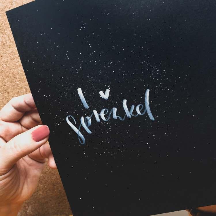 i love sprenkel - weisses Lettering mit vielen feinen Sprenkeln auf schwarzem Papier