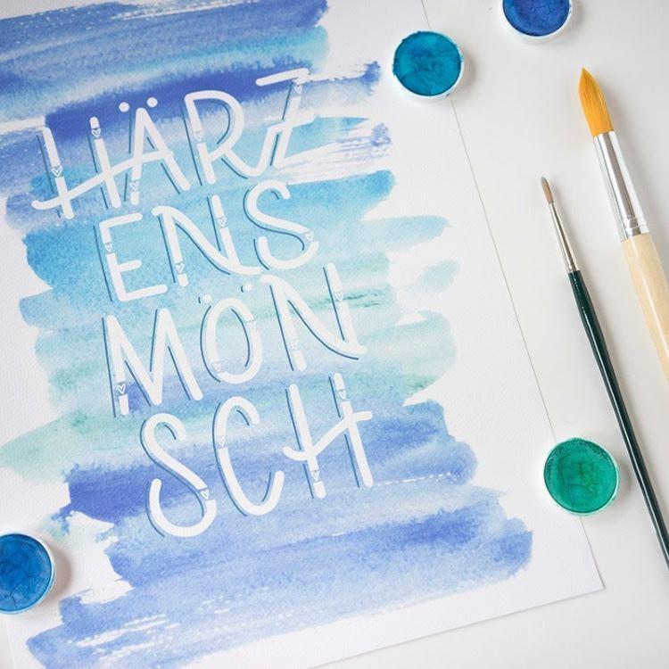 weisses Handlettering auf Schweizerdeutsch mit Aquarllhintergrund: Härzensmönsch