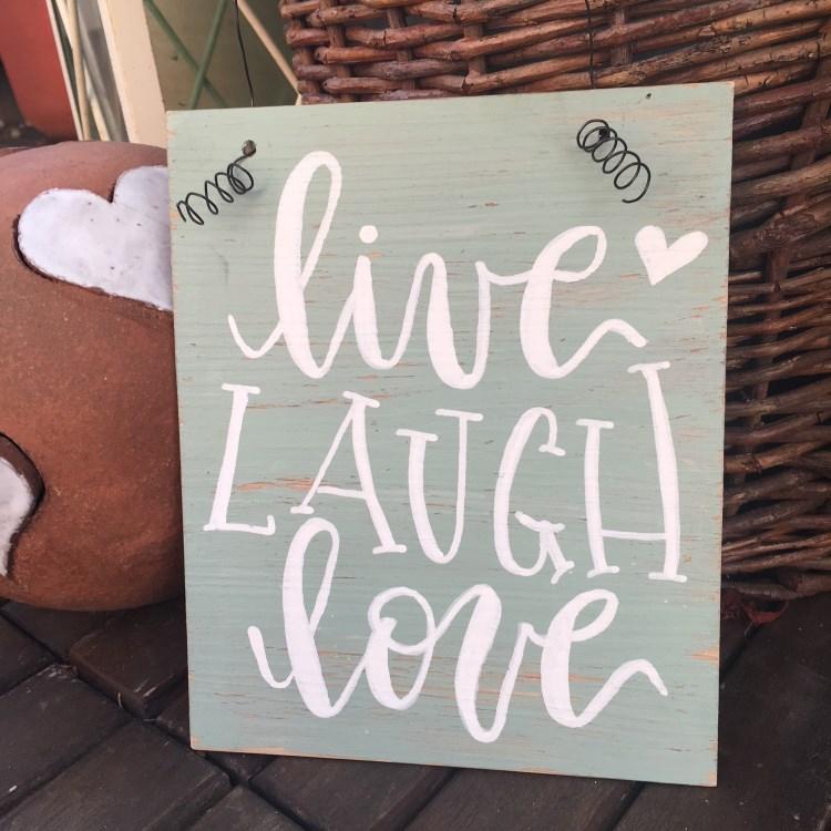 Schild mit einem Letering: live laugh love