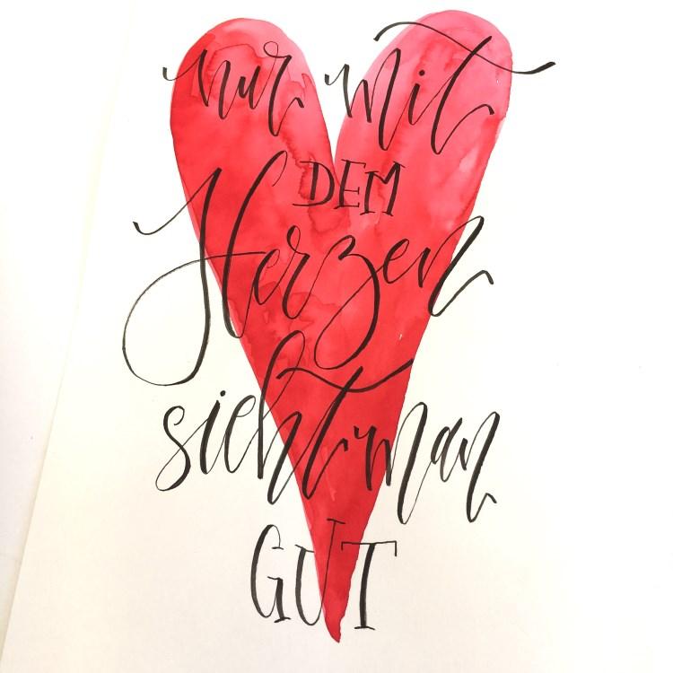 schwarzes Handlettering mit einem Herz im Hintergrund: nur mit dem Herzen sieht man gut