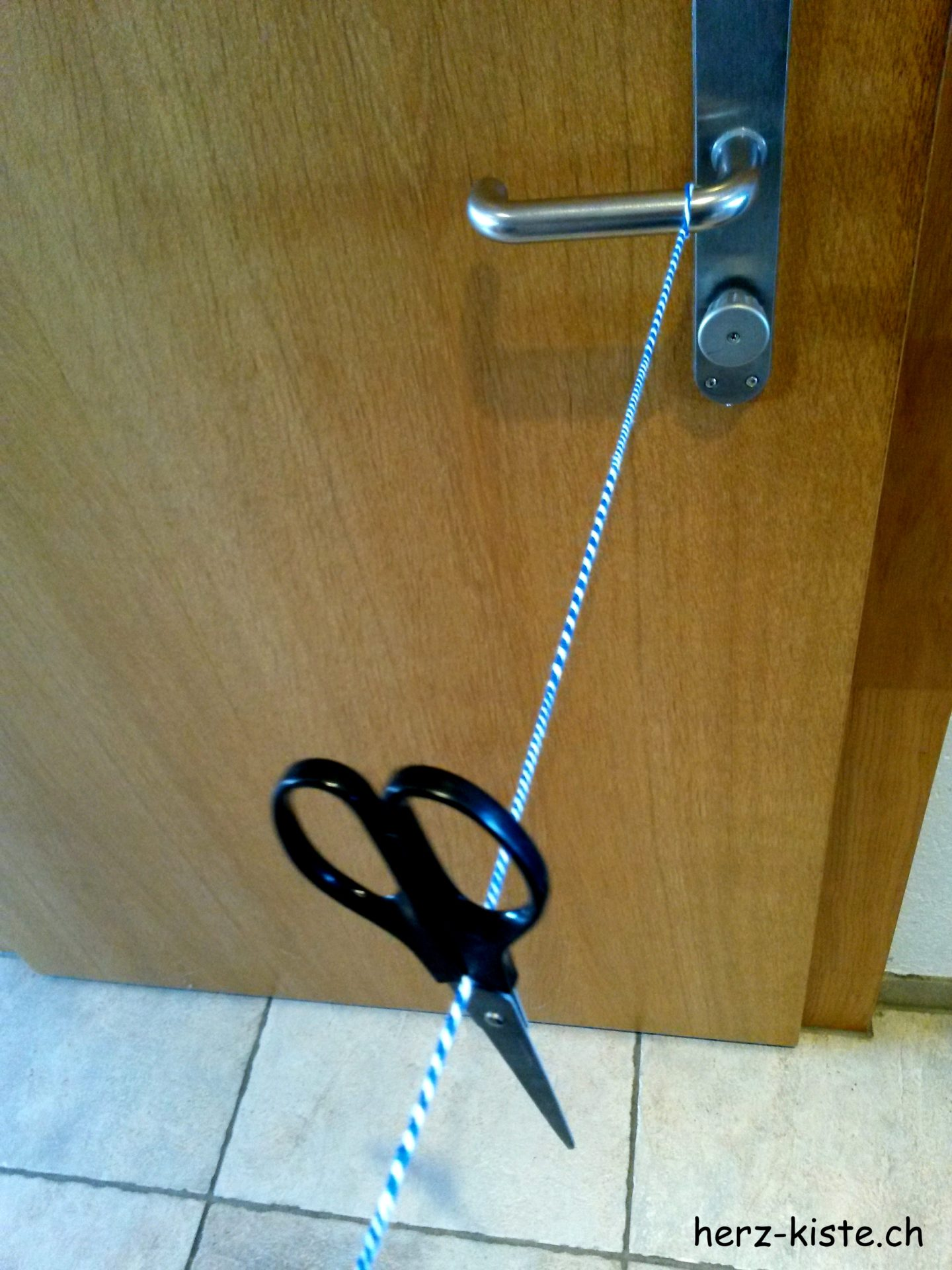 Kordel mit einer Schere an der Türe drehen