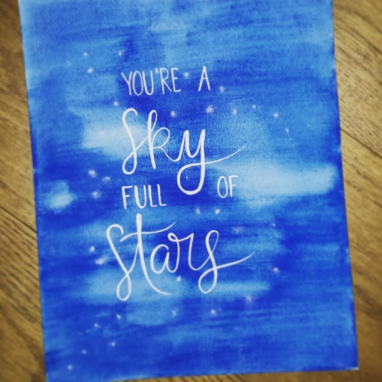 Handlettering in weiss auf blauem Aquarell Hintergrund: you're a sky full of stars