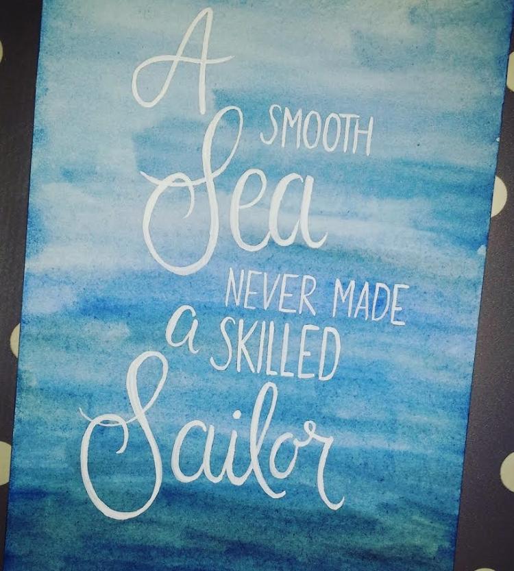 Handlettering auf blauem Aquarell Hintergrund: A smooth sea never made a skilled sailor