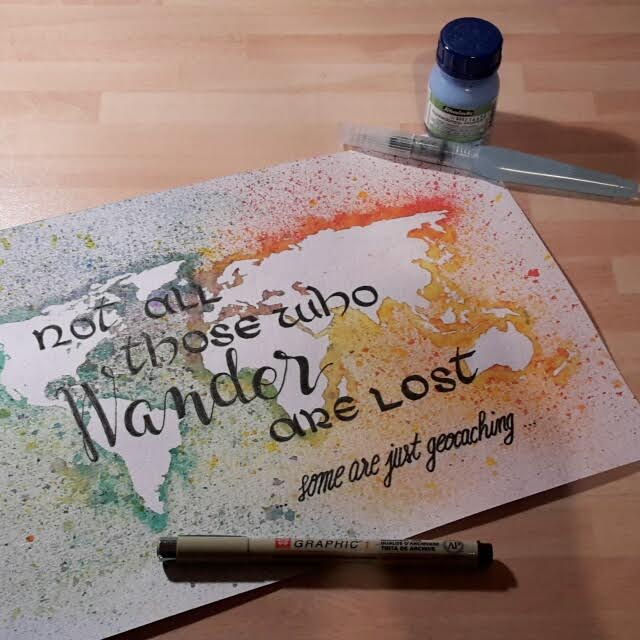 Handlettering auf einer Weltkarte - not all those who wander are lost some are just geocaching
