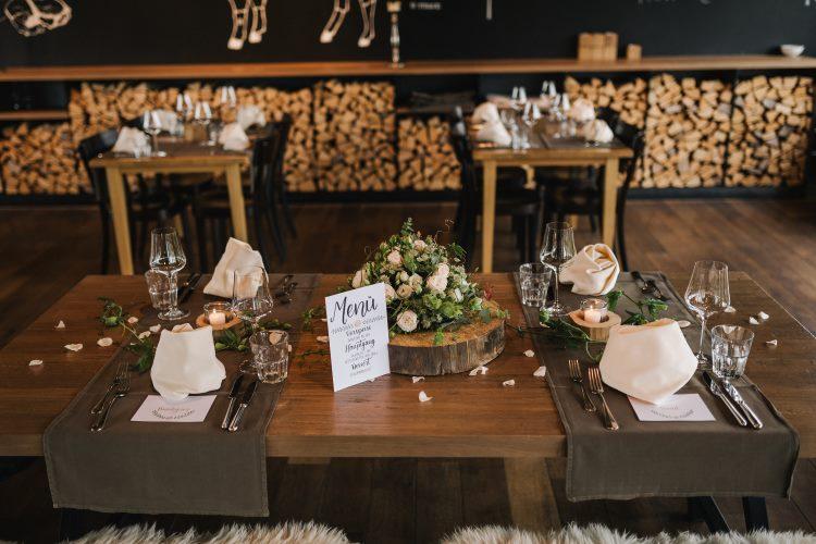 Gedeckte Tafel einer Hochzeit mit Menüschild im Lettering Stil