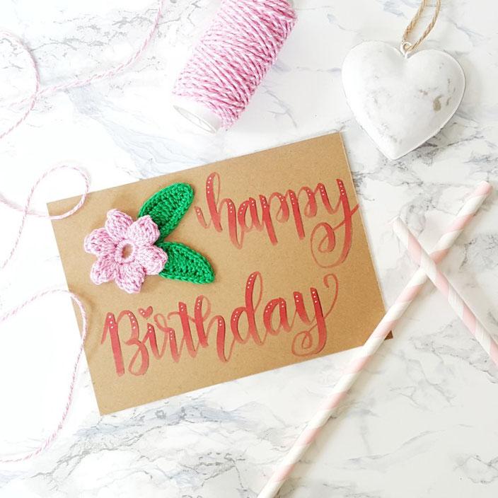 Happy birthday - Handlettering mit einer Häkelblume auf einer Karte