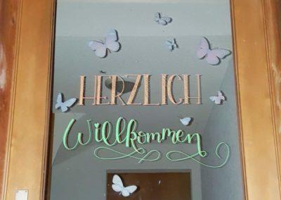 Herzlich Willkommen - Lettering auf einer Glas Tür