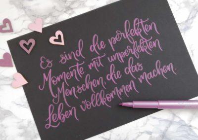 Lettering Spruch auf schwarzem Papier über perfekte Momente im Leben
